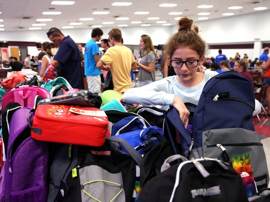 Hannah Templeton, 13, picks out a donated backpack for the first day of school while getting registered for school at the Flour Bluff Independent School District on Friday, September 1, 2017. She is from Port Aransas, TX, an area devastated by Hurricane Harvey. The school district in Port Aransas has declared school indefinitely closed.