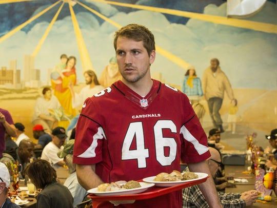 Arizona Cardinals player Aaron Brewer serves meals
