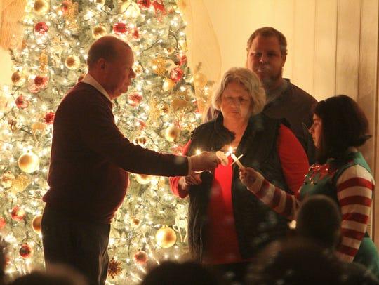 The Rev. Kurt Stutler, left, lights a candle at a service