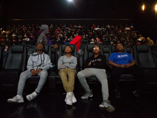 "From left, Blane Henry, Israel Reed, Darius Vialvia and Stephen Goodman watch movie previews before seeing ""Black Panther"" at the Penn Cinema Riverfront & IMAX on Monday."