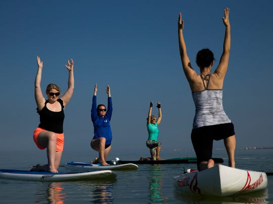Aimee Herrington, from left, Erin O'Neil, Cindy Gibson, and Marcy Boyd follow instructions from Jodi Ziajka, not pictured, a yoga instructor with the Naples Yoga Center, during her weekly paddle board yoga class at Delnor-Wiggins Pass State Park Sunday, March 18, 2018 in Naples.