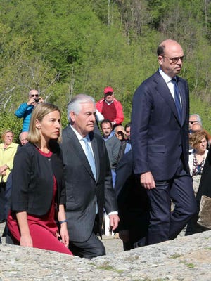 United States Secretary of State Rex Tillerson, center, flanked by European Union High Representative for Foreign Affairs Federica Mogherini, follow Italian Foreign Minister Angelino Alfano during a ceremony at the Sant'Anna di Stazzema memorial, dedicated to the victims of a 1944 Nazi massacre, in Sant'Anna di Stazzema, near Lucca, Italy, Monday, April 10, 2017.