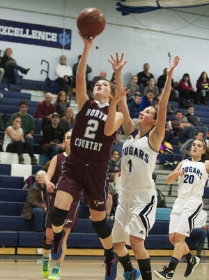 North Country's Carley Giroux (2) leaps past MMU's Ellie Devereux (1) for a layup during a high school girls basketball game between the North Country Falcons and the Mount Mansfield Cougars on Monday night.