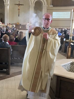 Most Rev. John Noonan, bishop of Orlando, swings the censer at the dedication of St. John the Evangelist Roman Catholic Church Saturday morning in Viera.