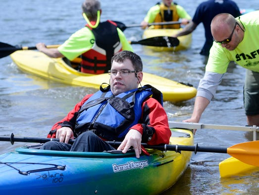 Brett Glirbas gets a little push onto shore from Cory Diedrich Sunday at an adaptive kayaking session as part of the South Dakota Canoe and Kayak Association paddling fair at Family Lake Park in Sioux Falls, June 8, 2014.