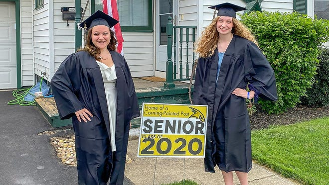 Mikayla Nelson (left) and Hannah Mealy (right) sport caps and gowns in front of their home. High school seniors have been forced to hold virtual graduations due to the COVID-19 pandemic.