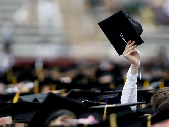 A student holds his cap in the air during a graduation ceremony.