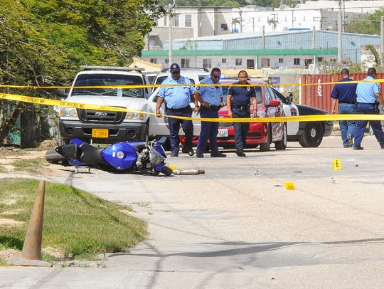 In this file photo, yellow crime scene tape stretches across Finegayen Road and a motorcycle is lying on the ground as Guam Police Department officers conduct an investigation of a shooting in Harmon of a motorcyclist by an airport police officer.