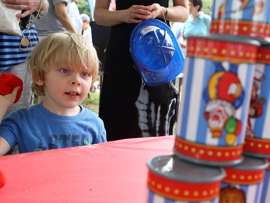 Gavin Dixon, 3, of Randolph, takes aim at clown cans as he plays a game at First Presbyterian Church of Succasunna as part of Olde Suckasunny Day.