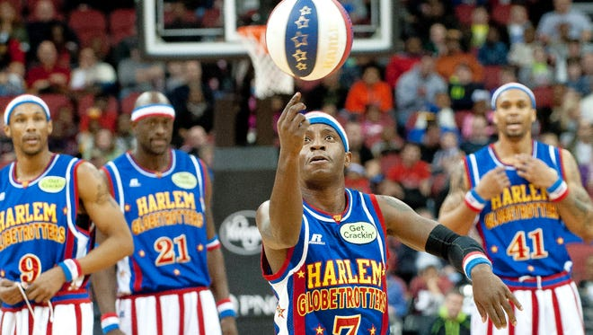 (Too Tall) Hall prepares to make a basket with nothing but his finger in a trick shot as his Harlem Globetrotters teammates look on. Jan. 18, 2014