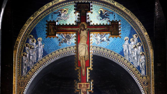 A cross with a painting of Jesus Christ hangs over the alter at Westminster Cathedral in London.