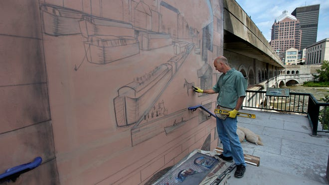 Syracuse mural artist Corky Goss is painting an Erie Canal mural with a scene form 1830s Rochester on a wall along the Broad St bridge next to Blue Cross Arena.  The mural will be finished in the next couple of weeks. Goss' company is On Sight Murals of Syracuse.