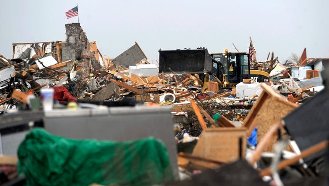 An endloader moves through debris covering the landscape of what was once a Washington, Ill.,  neighborhood on Nov. 21, 2013.