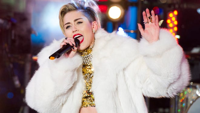 In this Dec. 31, 2013 file photo, Miley Cyrus performs in Times Square during New Year's Eve celebrations in New York. Cyrus is kicking off her North American Bangerz tour Feb. 14, 2014, in Vancouver.
