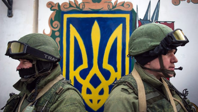 Armed men in military uniforms stand near the Ukrainian coat of arms in Perevalnoye, outside Simferopol, Ukraine. Russia approved the use of armed forces in the Crimean peninsula, which is part of Ukraine.