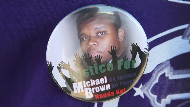 FERGUSON, MO - AUGUST 13:  A resident wears a button featuring a picture of Michael Brown during a press conference with Police Chief Thomas Jackson who was fielding questions related to the shooting death of Brown on August 13, 2014 in Ferguson, Missouri. Brown was shot and killed by a Ferguson police officer on Saturday. Ferguson has experienced three days of violent protests since the killing.  (Photo by Scott Olson/Getty Images) ORG XMIT: 506641261 ORIG FILE ID: 453571994