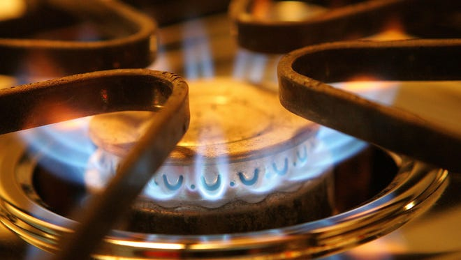A burner on a stove emits blue flames from natural gas.