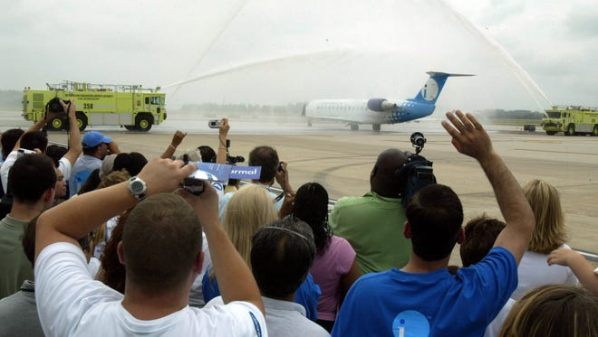 In this file photo from June 16, 2004, guests celebrate as a water cannon salute send off an Independence Air departure on the day the carrier launched service from Washington Dulles International Airport.