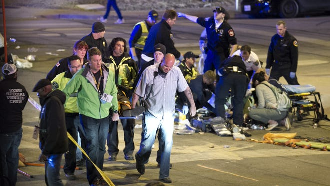 People carry a person who was struck by a car on Red River Street in downtown Austin, Texas, at SXSW on Wednesday March 12, 2014. Police say a man and woman have been killed after a suspected drunken driver fleeing from arrest crashed through barricades set up for the South By Southwest festival and struck the pair and others on a crowded street. (AP Photo/Austin American-Statesman, Jay Janner)