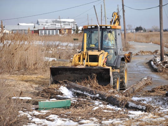 Contractor Bill Erhart, of Vineland, uses a backhoe to clear flood debris from the roadway in the Money Island section of Downe Township, Monday, Jan. 25.  Tidal flooding from the weekend's winter storm left the road covered with up to four feet of sand and debris, according to Erhart.