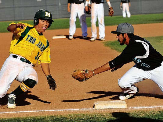 Jaime Guzman/For the Sun-News   Mayfield's Dominic Montez tries to slide around Oñate third baseman Jose Velasco in the first game of Thursday night's doubleheader at the Field of Dreams Baseball Complex.