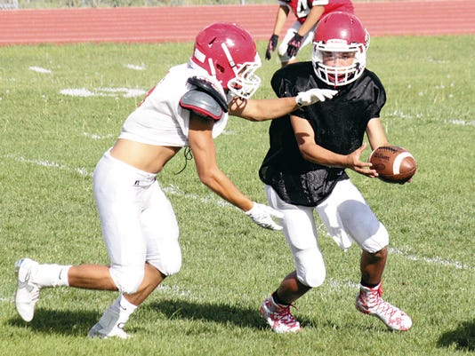 Danny Udero/Sun-News   Quarterback Andru Sanchez of Cobre hands the ball off to tailback Robert Rodriguez during practice Wednesday.