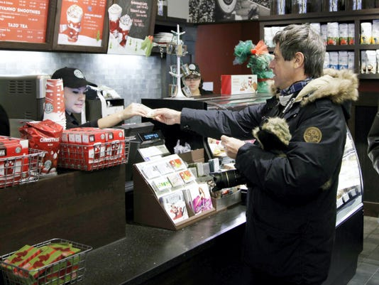 FILE - In this Dec. 6, 2010 file photo, a customer pays for a coffee beverage at Starbucks in the SoHo neighborhood of New York. A glitch that disabled registers at thousands of Starbucks stores on Friday, April 24, 2015 was a reminder of the invisible systems restaurants rely on to run increasingly sophisticated operations. (AP Photo/Mark Lennihan, File)