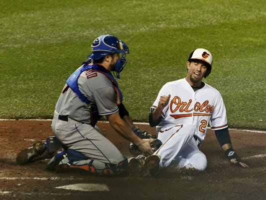The Orioles' J.J. Hardy, right, is tagged out by Mets catcher Travis d'Arnaud while trying to score on a single by Henry Urrutia during the fifth inning of Tuesday's game at Oriole Park at Camden Yards in Baltimore. The Mets won, 5-3.