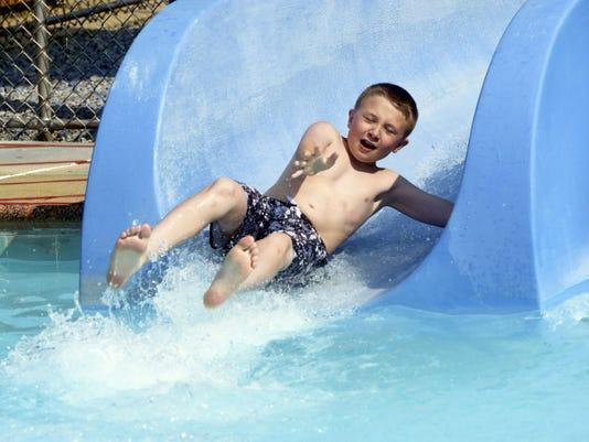 Kaden Wright, 10, of Chambersburg slides down the water slide at Chambersburg Municipal Pool on Wednesday, June 10, 2015. Ryan Blackwell - Public Opinion