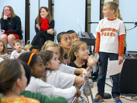 Christian Bucks, right, a second-grader at Roundtown Elementary School in Manchester Township, gives a presentation about his 'buddy bench' while students watch a digital presentation.