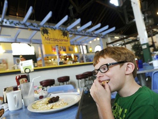Donovan Miller, 6, of East Prospect, chomps down on his pancakes during a breakfast visit to Mezzogiorno at Central Market on a recent Thursday.