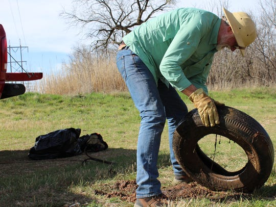 Jim Cooke drains muddy water from a tire pulled from