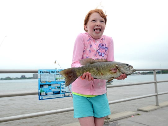 Emily Johnson, of Richmond, holds a smallmouth bass during the Summer Free Fishing Weekend.