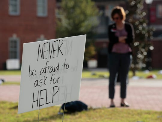 A woman looks over 400 backpacks set out in the quad of UL Lafayette Wednesday during Send Silence Packing, an event to raise awareness of suicide among college students.
