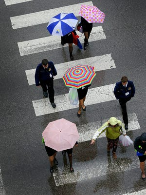 October showers brought out the umbrellas Thursday afternoon, Oct. 20, 2016, at Maryland and Illinois streets in Downtown Indianapolis. Thousands of blue FFA jackets by far outnumbered the umbrellas in the pedestrian traffic.