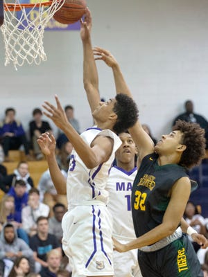 Male guard-forward Howard Fleming drives to the basket beating St. X forward James Shepherd to it. In on the play is Male forward Armani Rowan, center.Jan. 19, 2018