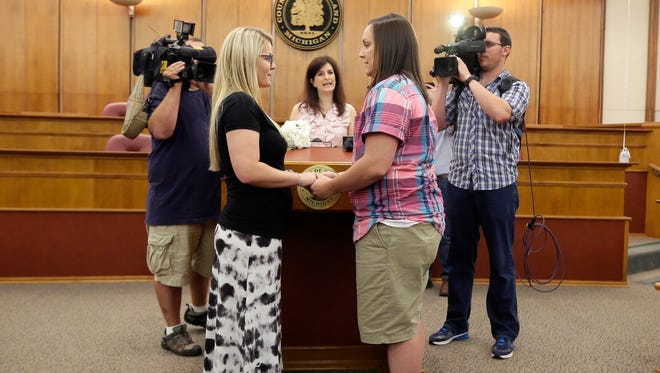 Oakland County Clerk Lisa Brown, center, marries Breanne Brodak, left, and Cortney Tucker in Pontiac, Mich., Friday, June 26, 2015, after the Supreme Court declared that same-sex couples have a right to marry anywhere in the United States. Michigan was one of 14 states enforcing a ban on same-sex marriage.