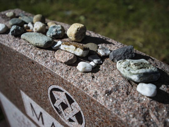Stones lie atop a grave marker at the Hebrew Holy Society
