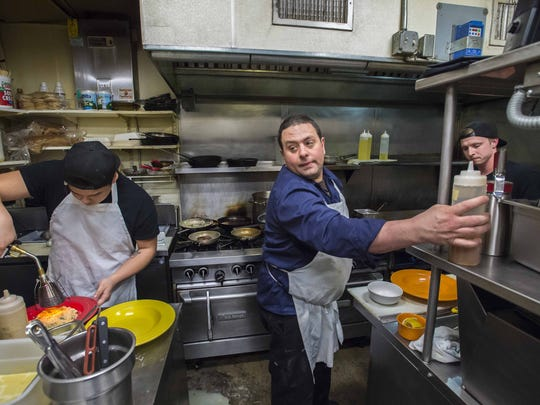 Chef Frank Pace, center, works in the kitchen of the