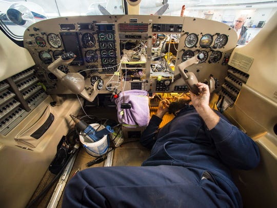 Aircraft mechanic Tom Laroche works inside a cockpit at Heritage Aviation at the Burlington International Airport in South Burlington on Wednesday, January 13, 2016.