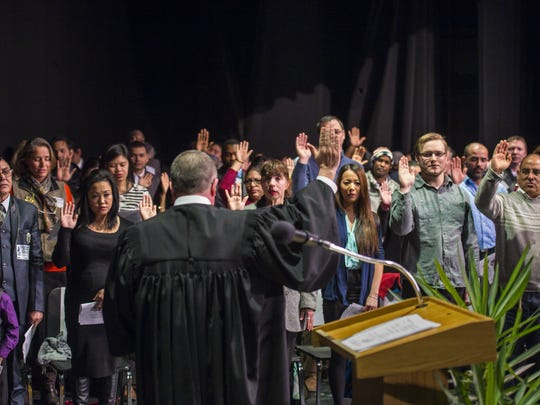 Fifty-five new American citizens take the oath of allegiance from U.S. Magistrate Judge John Conroy, center, during a naturalization ceremony at Burlington High School in Burlington on Thursday, February 11, 2016.