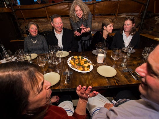 Sally Pollak takes a picture of New York strip steak served with pomme puree and basil salsa verde, part of the third course of dinner at Hen of the Wood in Waterbury on Thursday, March 31, 2016.