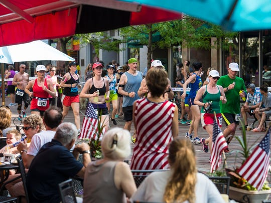 Runners in the People's United Bank Vermont City Marathon pass spectators seated at Leunig's Bistro and Cafe on Church Street in Burlington on Sunday, May 29, 2016.