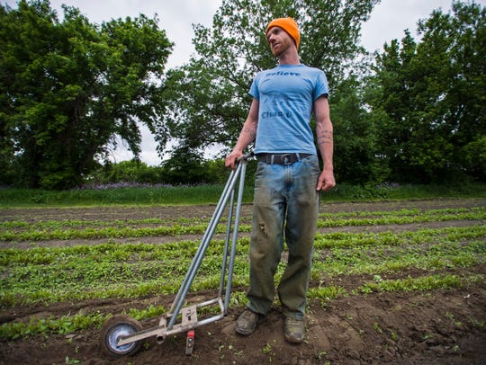 Mike Winters pauses from hoeing beets at The Juice