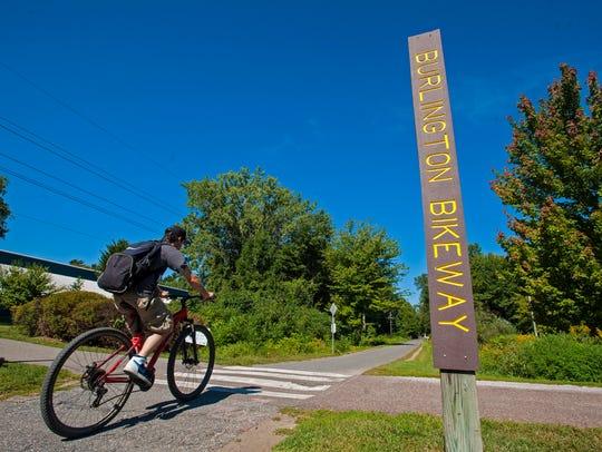 A cyclist rides along the Burlington bike path near