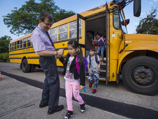 Principal Mark Trifilio greets students off the bus