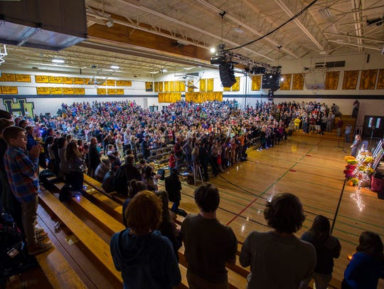 Mourners rise to give a standing ovation to Williston