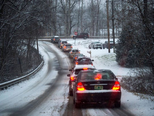 Traffic backs up at the intersection of Gov. Peck Highway and Route 117 in Richmond as snow falls on Monday, December 5, 2016.