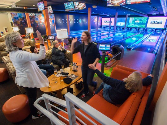 Anne Kraske of South Windsor, Connecticut, center, gets high fives after rolling a strike at Stowe Bowl in Stowe on Monday, March 27, 2017.