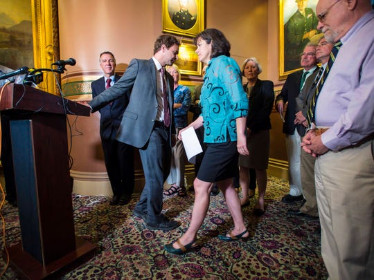 President Pro Tempore Tim Ashe, left, yields the podium to Speaker of the House Mitzi Johnson after they and Gov. Phil Scott announced a new state budget and school employee health care deal at the Statehouse in Montpelier on Wednesday, June 21, 2017.